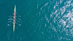 Aerial drone top down  view photo of yellow sport canoe operated by team of young women in emerald clear sea