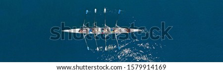 Aerial drone top ultra wide panoramic view of sport canoe rowing synchronous team of athletes competing in deep blue sea Foto stock ©