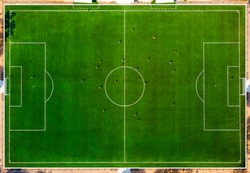 Aerial drone top view of mini football soccer field with playing people