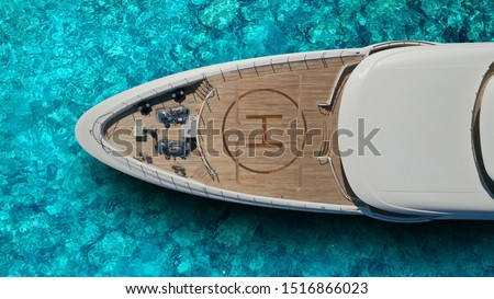 Aerial drone top view photo of large yacht - boat with helicopter landing area anchored in tropical exotic paradise bay with turquoise open sea