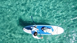 Aerial drone top view photo of man practising SUP or Stand Up Paddle with his cute dog in tropical exotic bay with turquoise sea