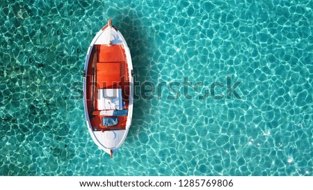 Aerial drone top view photo of red wooden traditional fishing boat in turquoise sea shore of Mykonos island, Cyclades, Greece Foto d'archivio ©