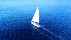 Aerial drone top view photo of sail boat sailing in mediterranean Aegean island of Santorini, Cyclades, Greece