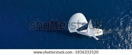 Aerial drone ultra wide panoramic photo of beautiful sail boat with white sails cruising deep blue sea near Mediterranean destination port Stockfoto ©