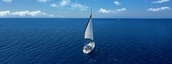 Aerial drone ultra wide panoramic photo of beautiful sailboat cruising the Aegean deep blue sea