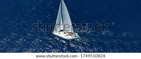 Aerial drone ultra wide photo of beautiful sail boat with white sails  sailing open ocean deep blue sea
