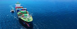 Aerial drone ultra wide photo of fully loaded container cargo ship cruising in open ocean deep blue sea