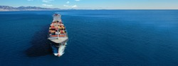 Aerial drone ultra wide photo of huge colourful truck size container tanker vessel cruising deep blue open ocean sea