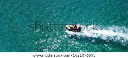 Aerial drone ultra wide photo of jet ski couple cruising in high speed in tropical exotic bay with emerald sea Сток-фото ©