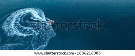 Aerial drone ultra wide photo of jet ski watercraft performing extreme manoeuvres in deep blue bay with calm sea at dusk Сток-фото ©