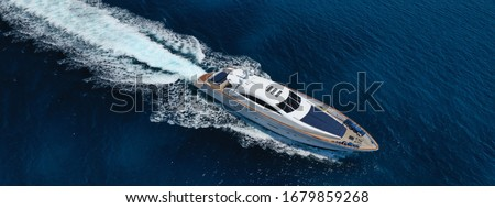 Aerial drone ultra wide photo of luxury yacht cruising in deep blue sea near Mediterranean Aegean island Stock photo ©