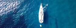 Aerial drone ultra wide photo of sail boat anchored in deep blue Mediterranean Sea