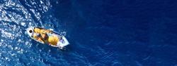 Aerial drone ultra wide photo of traditional wooden fishing boat cruising in deep blue sea near port of Mykonos island, Cyclades, Greece