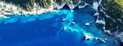 Aerial drone ultra wide photo of tropical white rocky bay of blue lagoon with turquoise clear waters, white volcanic caves and sail boats docked, island of Paxos, Ionian, Greece