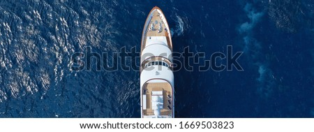 Aerial drone ultra wide top down photo of luxury yacht with wooden deck anchored in Aegean island with deep blue sea, Greece
