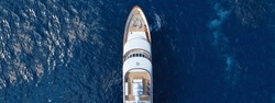 Aerial drone ultra wide top down photo of luxury yacht with wooden deck docked in Aegean island with deep blue sea, Greece