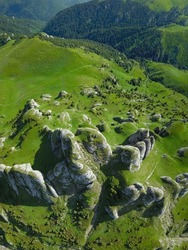 Aerial drone, vertical panorama of Ciucas Mountains peaks. On the alpine grasslands, eroded calcareous boulders are forming interesting stone conglomerations. Carpathians, Romania.