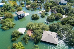 Aerial drone view above a natural disaster. Flooded homes with water up to the roof tops massive flooding all along the Colorado River with search and rescue out looking for survivors