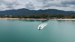 Aerial drone view angle of speeding white speed boat in green waters of the coast of Koh Samui island in Thailand