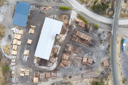 aerial drone view from top to sawmill with tree wood trunk staples around