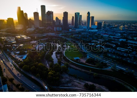 aerial drone view high above Houston Texas Downtown Sunrise Sunburst over Urban Sprawl Interstate roads , Buffalo Bayou River Park , and Downtown Skyline background
