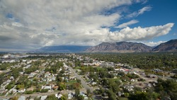 Aerial drone view high above the neighborhoods of Ogden , Utah looking towards downtown and the commercial district with a beautiful sky and clouds