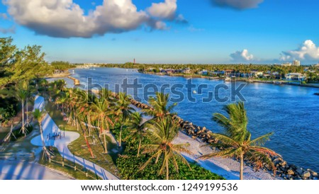 Aerial drone view Jupiter Inlet, Jupiter Beach Park, Florida, USA. Jupiter Lighthouse in distance.