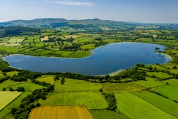 Aerial drone view of a lake surrounded by green farmland and fields in rural Wales (Llangorse Lake)