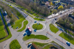 aerial drone view of a roundabout road way in The Netherlands, zuid holland / Utrecht. village of Wilnis with traffic and transportation. infrastructure from above road plus  bicycle lane