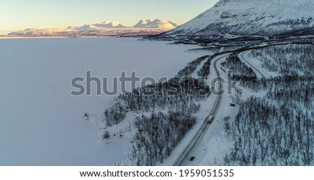 Aerial drone view of a truck driving at the gate of lapponia, the Lapporten mountains, Tornetrask lake, sunny winter evening, in Lappland, Sweden Stock foto ©