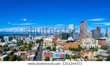 Aerial drone view of a wide panoramic view of the Denver , Colorado downtown skyline cityscape towers and skyscrapers rising on right and Colorado state Capitol building on left with Rocky Mountains