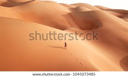 Aerial drone view of a young athletic caucasian tourist in shorts and straw hat hiking in Liwa desert dunes. Abu Dhabi, UAE.
