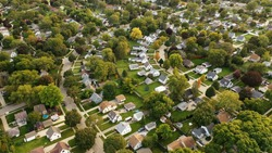Aerial drone view of American suburban neighborhood at daytime. Establishing shot of America's  suburb. Residential single family houses pattern