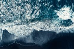 Aerial drone view of Atlantic ocean waves washing black basaltic sand beach, Iceland.