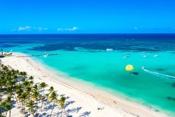 Aerial drone view of beautiful caribbean tropical beach with straw umbrellas, palms and boats. Bavaro, Punta Cana, Dominican Republic. Vacation background.