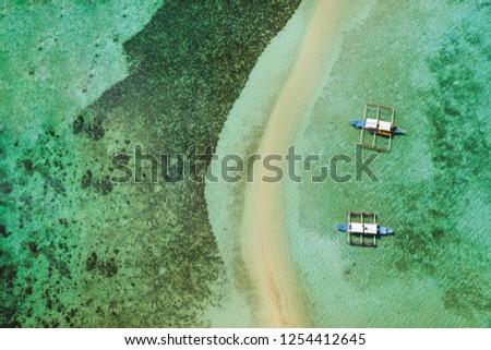Aerial drone view of boats moored at turquoise coastal waters and coral reef in El Nido archipelago tourist destination of Snake Island. El Nido, Palawan, Philippines.