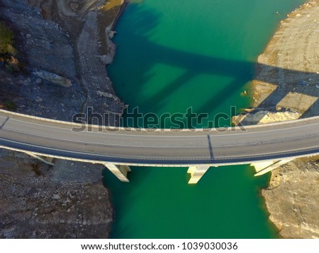 Aerial drone view of bridge over turquoise waters in Llosa del Cavall Lake, near Barcelona, Catalonia, Europe. Dry lake for climate change warming. Beautiful, bridge adventure and travel #1039030036