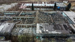 Aerial drone view of burned and abandoned industrial complex. Former factory. Remnants of burnt down building. Fire damage. Damaged industrial halls.