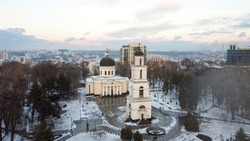 Aerial drone view of Chisinau downtown in winter. Panorama view of central park with snow, trees and multiple walking people, belltower, cathedral, buildings on the background. Moldova