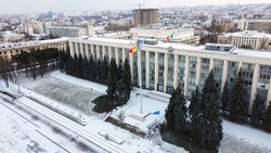 Aerial drone view of Chisinau in winter. Panorama view of the Goverment building, snow, multiple buildings on the background, road, bare trees. Moldova