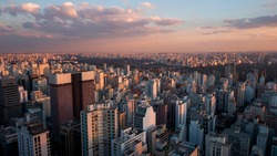 Aerial drone view of cityscape bathed in magic hour sunset light. Skyscrapers of landmark Avenida Paulista in major metropolitan city of Sao Paulo, Brazil.