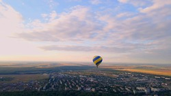 Aerial drone view of colorful hot air balloon flying over green park in small european city at summer sunset, Kiev region, Ukraine