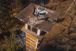 Aerial drone view of daredevils on the top of an abandoned ski jumping hill in siska, slovenia. dangerous maneouvres and stunts on buildings.