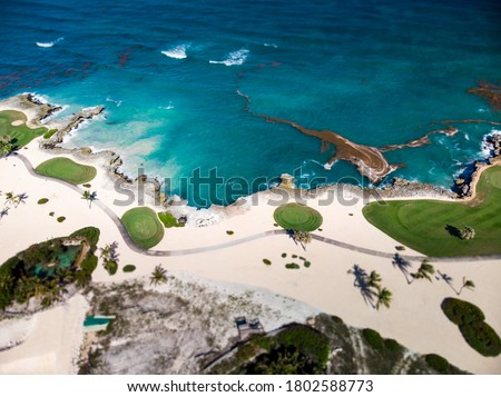 Aerial drone view of golf course at the rocky shore of Caribbean Sea with spots of algae (seaweed) on the water surface in Cap Cana, Punta Cana, Dominican Republic
