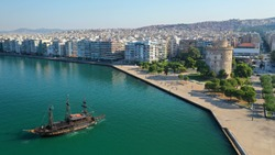 Aerial drone view of iconic historic landmark - old byzantine White Tower of Thessaloniki or Salonica with traditional tourist boats travelling Thermaikos gulf, North Greece