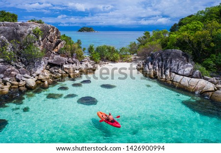 Aerial drone view of in kayak in crystal clear lagoon sea water during summer day near Koh Lipe island in Thailand. Travel tropical island holiday concept