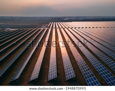 Aerial drone view of large solar panels at a solar farm at bright spring sunset. Solar cell power plants, colorful HDR photo