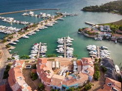 Aerial drone view of luxury yacht marina (port) with european style buildings in Casa de Campo, La Romana, Dominican Republic