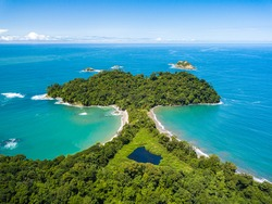 Aerial Drone view of Manuel Antonio National Park in Costa Rica. The best Tourist Attraction and Nature Reserve with lots of Wildlife, Tropical Plants and paradisiacal Beaches on the Pacific Coast.