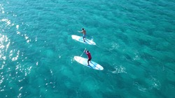 Aerial drone view of 2 men exercising sup board in turquoise tropical clear open sea